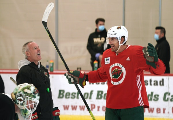 Wild coach Dean Evason laughs with Marcus Foligno before a practice this summer ahead of the NHL's restart.