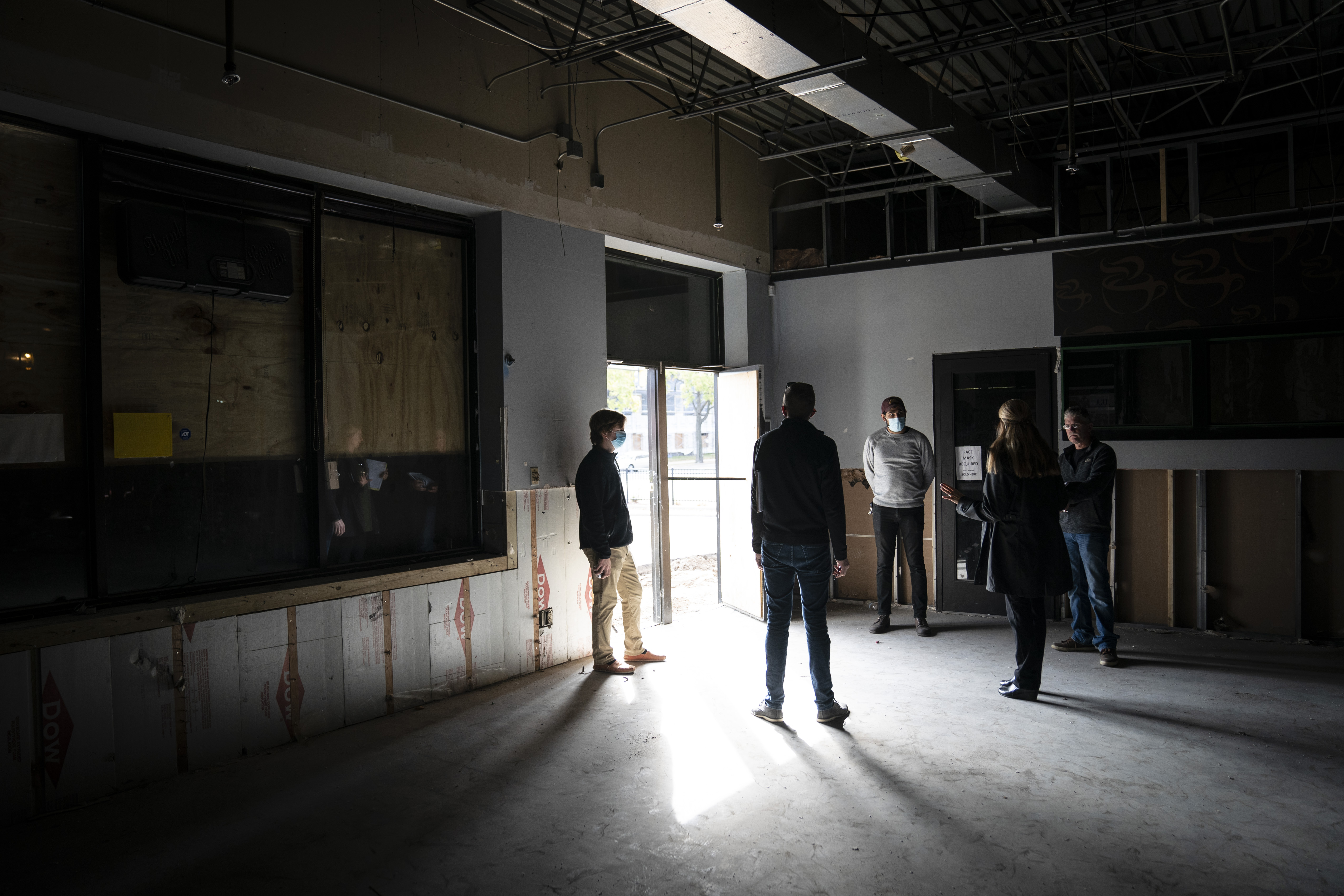 A to Z Gas Stop owner Joe Zerka (in white mask) talked with consultants and builders in the empty shell of his business in Minneapolis. The electricity had yet to be turned on.