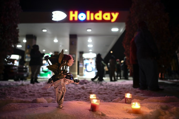 Flowers are left Thursday at a Holiday gas station near where Dolal Idd, 23, was shot and killed by Minneapolis police the night before during a traff