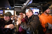 Dean Wedul of Lakeville, right of center, lifted his drink with friends at the bar at the Alibi Drinkery in Lakeville on Dec. 16.