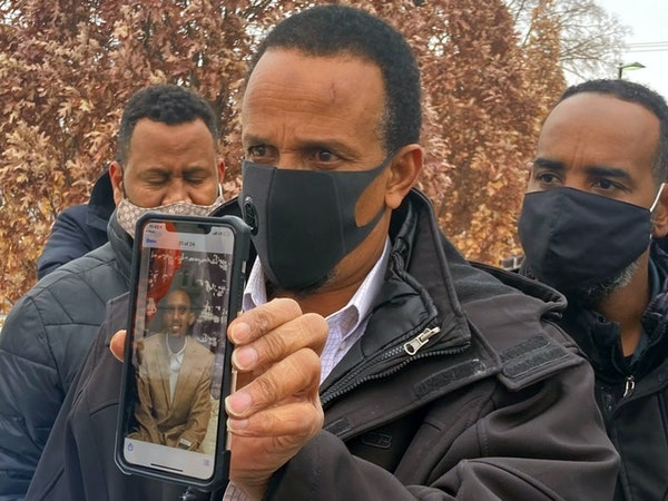 Bayle Gelle, surrounded by supporters, displays a picture of his son, 22-year-old Dolal Idd, who was killed by Minneapolis police at the Holiday gas s