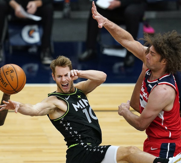 Minnesota Timberwolves forward Jake Layman (10) passed the ball off as he collided with Washington Wizards center Robin Lopez (15) in the second quart