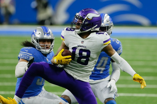 Vikings wide receiver Justin Jefferson makes a catch as Lions outside linebacker Jahlani Tavai, left, and cornerback Amani Oruwariye defend during the