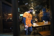 A masked employee cleaned a table at Blarney Pub & Grill in Dinkytown on Nov. 13. Gov. Tim Walz is planning to announce Wednesday that he will loosen