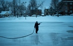 Top, park keeper Leslee Hagberg sprayed another layer of water on a Minneapolis skating rink. Above, Ali Hassan helped keep his 4-year-old daughter, S
