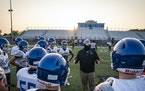 Face masks pose dangers for athletes during competition, the writer says. Above, the Woodbury High School football team in the fall.