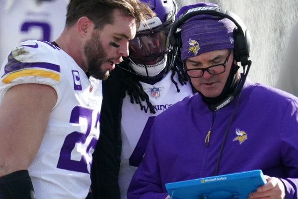 Vikings coach Mike Zimmer (right, with safety Harrison Smith) got career years from several offensive skill players, but his defense was decimated by