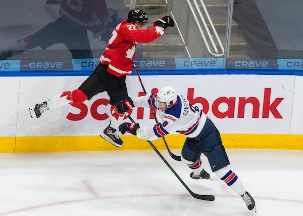 Canada's Dylan Cozens leaped as he was checked by the United States' Jake Sanderson during the second period of the Americans' 2-0 victory in th