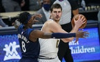 Nuggets center Nikola Jokic looked to pass as Timberwolves forward Jarred Vanderbilt defended him Tuesday. Jokic didn't have to pass often, collecti