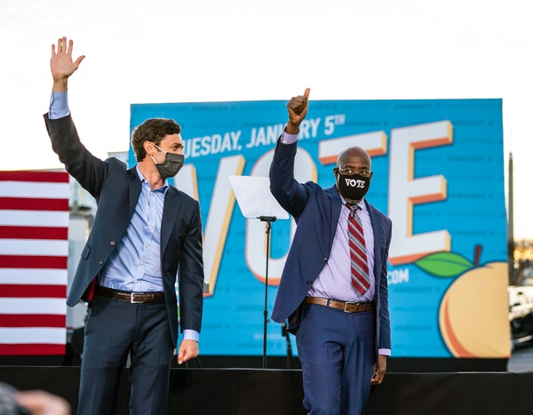 From left, Democratic Senate candidates Jon Ossoff and the Rev. Raphael Warnock wave after a campaign event with President-elect Joe Biden in Atlanta