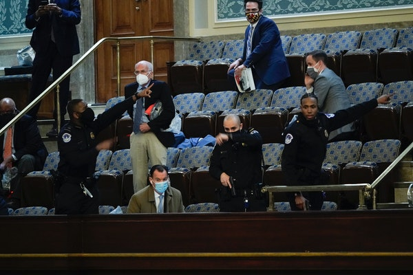 Lawmakers prepare to evacuate the House gallery as protesters try to break into the House Chamber at the U.S. Capitol on Wednesday, Jan. 6, 2021, in W