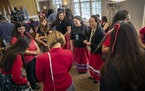Native women, dressed in red, gathered before a ceremonial bill signing to launch the first official meeting of the state Missing and Murdered Indigen