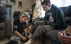 Megan Matson helped her husband Waseca Police Officer Arik Matson put on his shoes at their home in Freeborn.