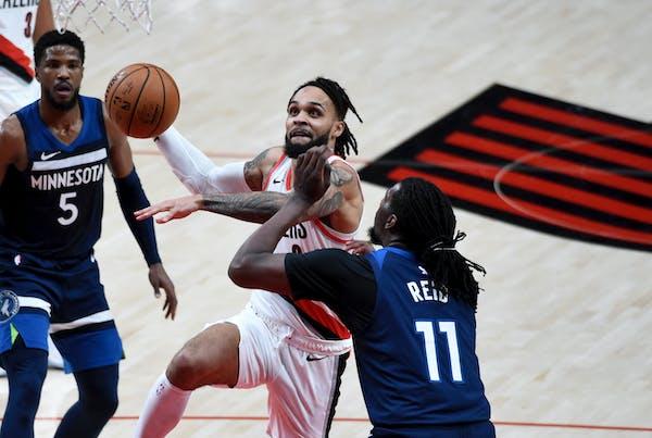 Portland Trail Blazers guard Gary Trent Jr., left, drives to the basket against Timberwolves center Naz Reid