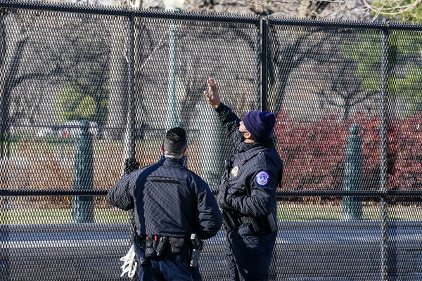 Capitol Police officers look at fencing that was installed around the exterior of the Capitol grounds, Thursday, Jan. 7, 2021 in Washington.