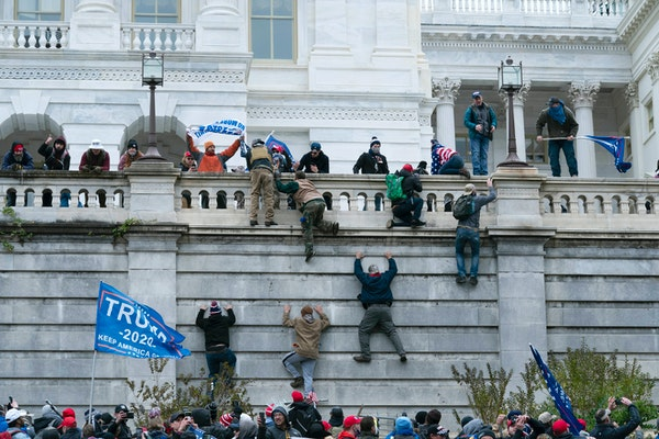 Supporters of President Donald Trump climb the west wall of the the U.S.Capitolon Wednesday, Jan. 6, 2021, in Washington.