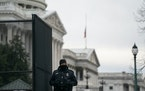 A U.S. Capitol Police officer guards a gate to the Capitol in Washington on Friday, Jan. 8, 2021, while wearing a black band over his badge to mark th
