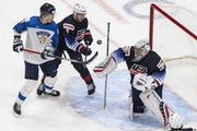 United States goalie Spencer Knight (30) makes a save as Finland's Henri Nikkanen (28) and United States' Brock Faber (11) battle in front of the