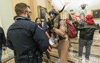 Supporters of President Donald Trump are confronted by U.S. Capitol Police officers outside the Senate Chamber inside the Capitol in Washington. Jacob