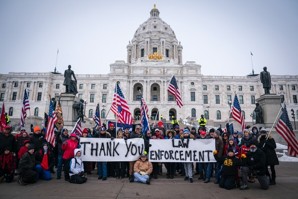 People posed with signs thanking law enforcement Saturday as Minnesota state troopers stood guard outside the State Capitol during a rally supporting