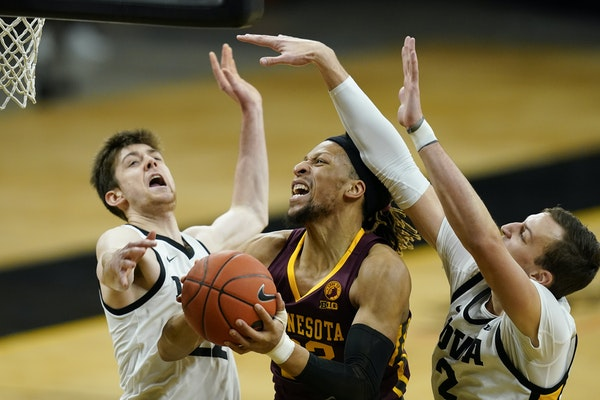 Minnesota forward Brandon Johnson, center, drives to the basket between Iowa forward Patrick McCaffery, left, and forward Jack Nunge, right, during th