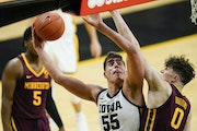 Iowa center Luka Garza put up a hook shot over Gopers center Liam Robbins in the second half Sunday in Iowa City. The Hawkeyes won 86-71.