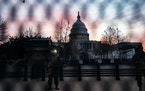 National Guard troops, seen through a security fence at the U.S. Capitol early Monday morning, Jan. 11, 2021.