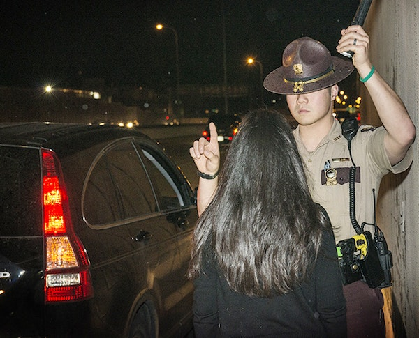 A State Trooper conducts a field sobriety test on a driver.