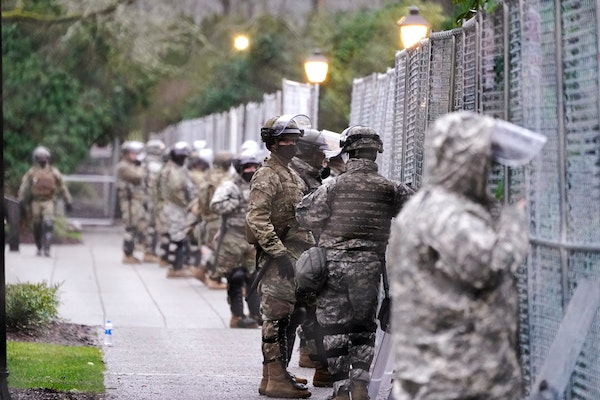 Members of the Washington National Guard stand at a fence surrounding the Capitol in anticipation of protests Monday, Jan. 11, 2021, in Olympia, Wash.