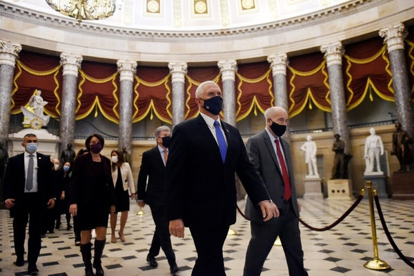 Vice President MikePence walked back from the House Chamber followed by a Senate procession carrying boxes of electoral votes, on Wednesday, Jan. 7,