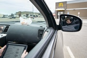 Colton Rebarich worked on choir homework in his mom's car in a McDonalds parking lot in Virginia, MN on Monday. They have to sit in the parking lot