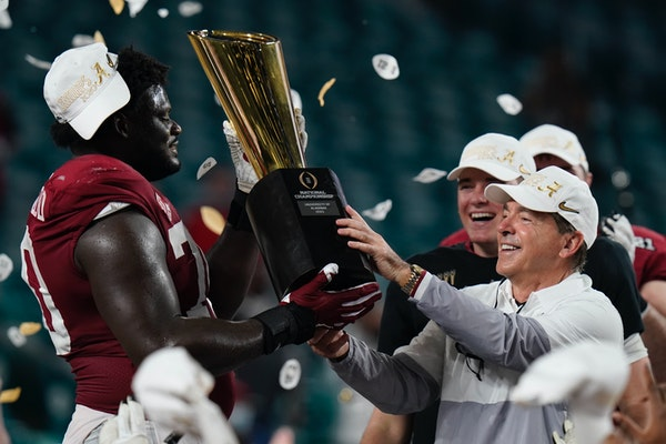 Alabama head coach Nick Saban and offensive lineman Alex Leatherwood hold the trophy after their win against Ohio State in an NCAA College Football Pl