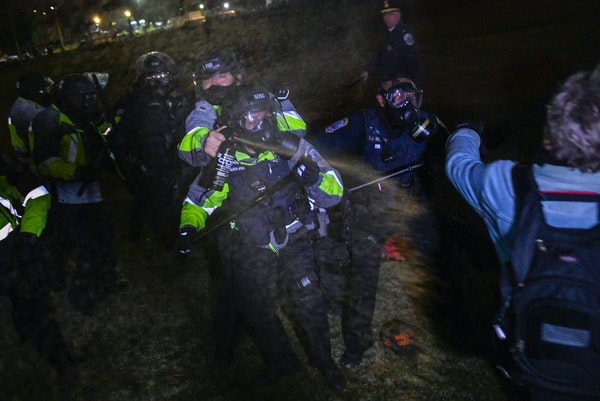 Police use pepper spray to help disburse a mob of Trump supporters from the Capitol grounds in Washington on Wednesday, Jan. 6, 2021, after they breac