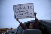 Hamza Dirie, 9, a fourth grader, held a sign out his father's truck's window calling to empower school teachers during Tuesday night's rally. �