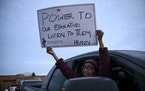 Hamza Dirie, 9, a fourth-grader, held a sign out his father's truck's window calling to empower school teachers during Tuesday night's rally.