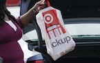 A Target employee places a curbside pickup purchase into the trunk of a customer in Jackson, Miss., in November. (AP Photo/Rogelio V. Solis)