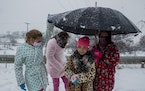 Children shelter under an umbrella as the snow falls at the Canada Real shanty town, outside Madrid, Spain, Friday, Jan. 8, 2021. Canada Real, a shant