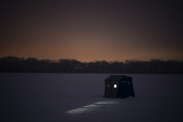 An angler fished inside a portable ice fishing shelter on Cedar Lake in Minneapolis.   ]  JEFF WHEELER • jeff.wheeler@startribune.com