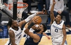 Timberwolves center Karl-Anthony Towns put up a second quarter shot while defended by Memphis' Xavier Tillman (2) and De'Anthony Melton