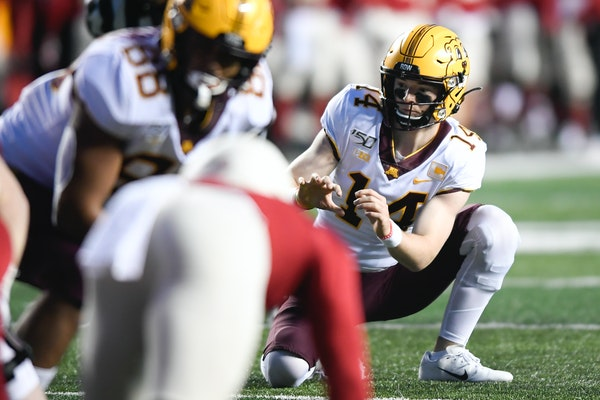 Gophers holder Casey O'Brien set up for an extra point during a game in 2019.