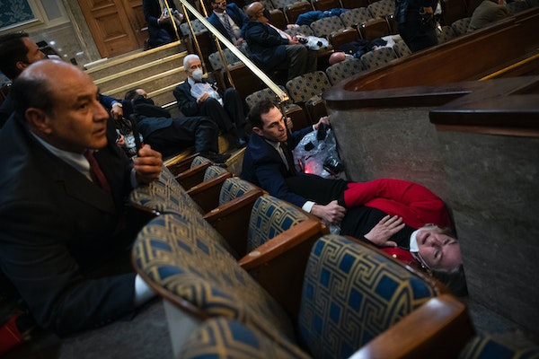 Rep. Jason Crow, D-Colo., comforted Rep. Susan Wild, D-Pa., while taking cover as protesters disrupted the joint session of Congress to certify the El