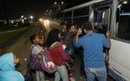 Migrants trying to reach the U.S. border board a public transport bus on the highway to Choloma, Honduras, Thursday, Jan. 14, 2021. About 200 Honduran