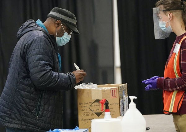 James Page, left of the Cultural Wellness Center, turned in his saliva sample after taking a COVID-19 test while touring the testing facility Tuesday