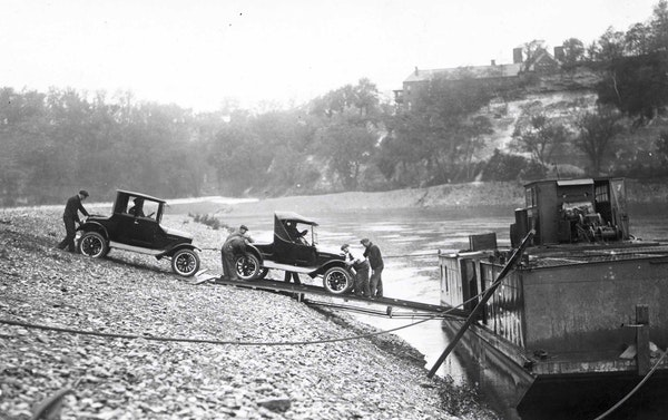 Ford cars built at the St. Paul plant are loaded on to river barges on the Mississippi River in 1925.