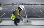 Cedar Creek Energy crew, including Reed Martin, installed solar panels on the roof of Brin Glass, Monday, April 6, 2020 in Fridley, MN. ELIZABETH FLOR