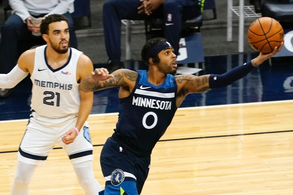 Tyus Jones ooks on as the Timberwolves' D'Angelo Russell lays up a shot in the second half