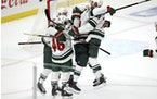 Wild defenseman Mathew Dumba, right, leaps into the arms of left wing Kirill Kaprizov, second from right, after an overtime goal against the Los Angel