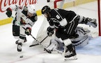 Minnesota Wild left wing Jordan Greenway, left, controls the puck against Los Angeles Kings defenseman Drew Doughty (8) during overtime in an NHL hock