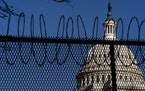 The Dome of the Capitol Building is visible through razor wire installed on top of fencing on Capitol Hill in Washington, Thursday, Jan. 14, 2021. (AP