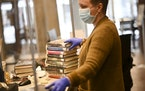 Alex Riley, an associate librarian with the Arvonne Fraser Library in Minneapolis, processed returned books.